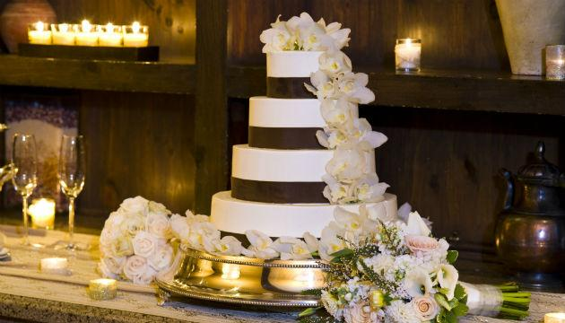 Having a large, white wedding cake is traditional but if it's not important to you, consider skipping it altogether. Many catering or reception dinners include a dessert or you could downsize to a smaller cake just for the couple to cut. Other options include cupcakes, cake pops or other treats, but having these professionally done can be almost as expensive as the original cake. Keep in mind that many of your guests will not have a piece of cake or cupcake, especially if they have already had dessert as part of their meal.