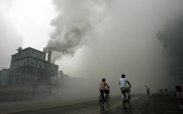 Cyclists pass through thick pollution from a factory in Yutian, China on July 18, 2006 (AFP Photo/Peter Parks)