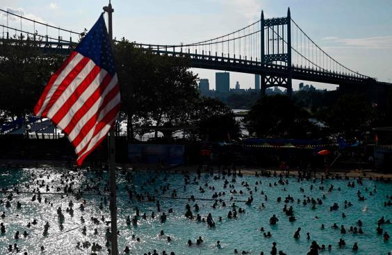 A US flag flies overhead as people enjoy the Astoria Pool on a hot afternoon in the New York City borough of Queens (AFP/Getty Images)