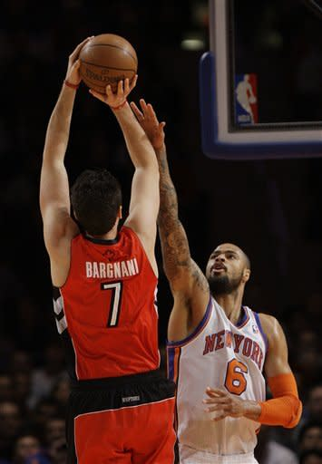 Toronto Raptors' Andrea Bargnani (7) shoots over New York Knicks' Tyson Chandler (6) during the first half of an NBA basketball game Monday, Jan. 2, 2012, in New York. (AP Photo/Frank Franklin II)