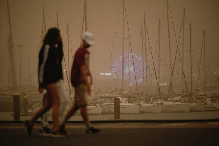 Yachts and boats sit moored in a cloud of red dust in Santa Cruz de Tenerife, Spain, Sunday, Feb. 23, 2020.