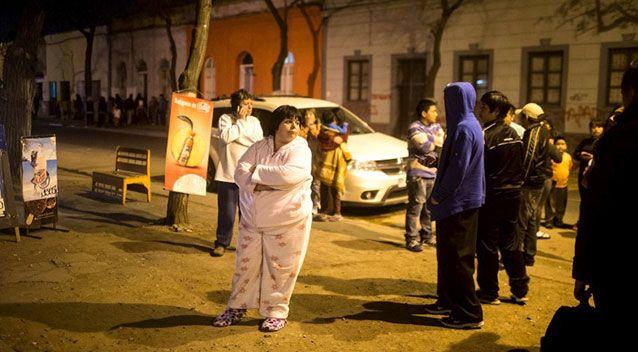 Residents stand on a street outside their houses after an earthquake hit Chile's central zone, in Santiago, Chile. Photo: Reuters