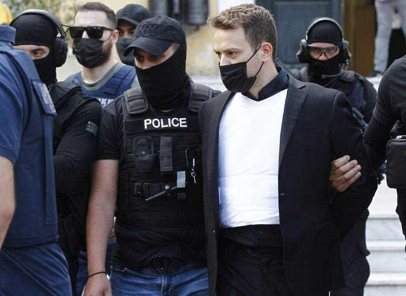 Babis Anagnostopoulos, husband of murdered Caroline Crouch, is escorted out of the prosecutor's office, Athens, Greece, on June 18, 2021.
