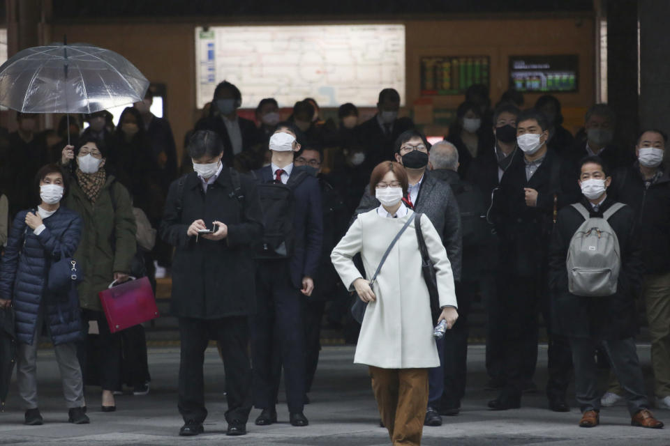 People wearing face masks to protect against the spread of the coronavirus wait for signals to turn to green at a crossing in Tokyo, Monday, Feb. 15, 2021. The Japanese economy grew at an annual rate of 12.7% in October-December, marking the second straight quarter of growth, amid a recovery from the slump caused by the coronavirus pandemic, according to government data released Monday. (AP Photo/Koji Sasahara)