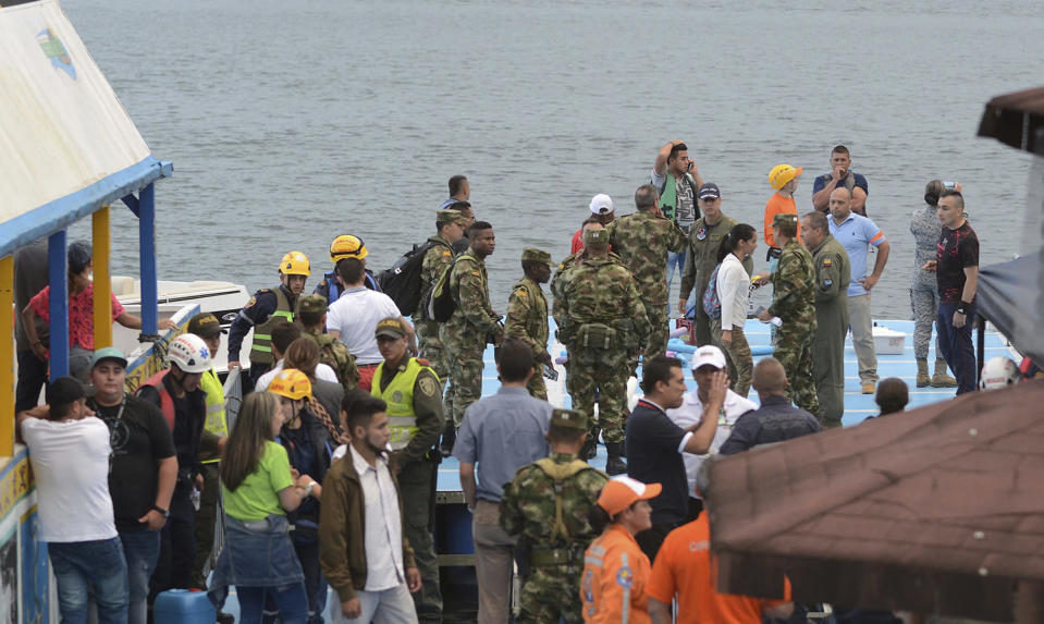 <p>Soldiers and rescue workers stand at the dock of the reservoir where a ferry sank, during search efforts in Guatape, Colombia, Sunday, June 25, 2017. (Luis Benavides/AP) </p>