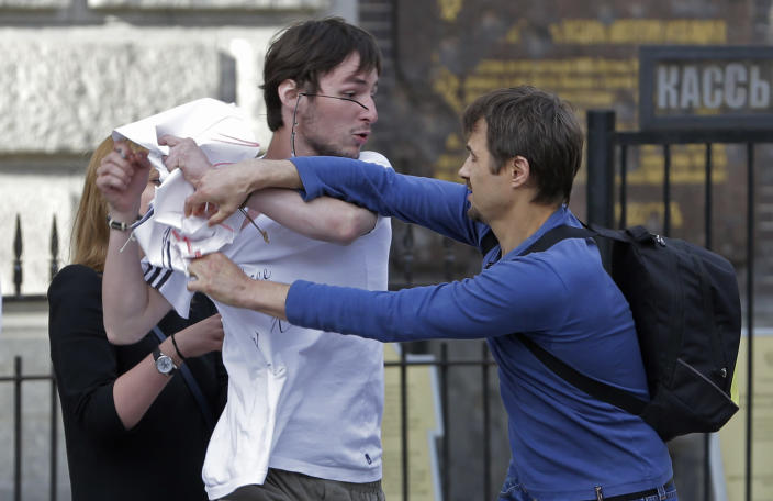 An Orthodox believer, right, pulls at a poster held by a demonstrator, whose spectacles have been knocked from his head, standing in a picket in support of the Russian punk group Pussy Riot whose members face prison for a stunt against President Vladimir Putin, in front of the Savior of Spilled Blood Cathedral in St.Petersburg, Russia, Friday, Aug. 17, 2012. A Moscow judge has sentenced each of three members of the provocative punk band Pussy Riot to two years in prison on hooliganism charges following a trial that has drawn international outrage as an emblem of Russia's intolerance to dissent. ( AP Photo/Dmitry Lovetsky)