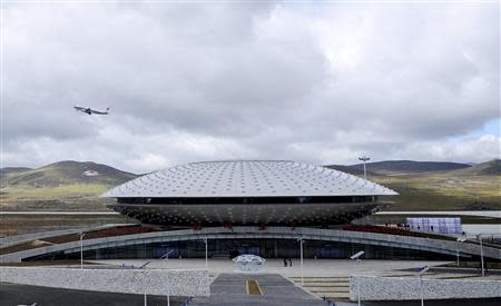 A plane takes off from the terminal of Daocheng Yading Airport in Daocheng county of Garze Tibetan Autonomous Prefecture, Sichuan province September 16, 2013. The airport, at 4,411 metres (14,472 feet) above sea level, surpassed the Qamdo Bangda Airport which has an altitude of 4,334 metres (14,219 feet), and became the highest airport in the world after its inauguration on Monday, according to local media. REUTERS/China Daily