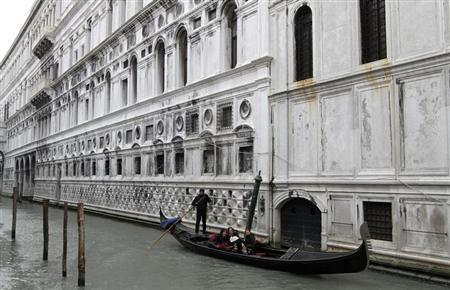 A gondolier rows his gondola in a canal in Venice