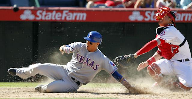 Texas Rangers' Leonys Martin, left, scores under the tag of Los Angeles Angels catcher Hank Conger on a sacrifice fly in the seventh inning during a baseball game Sunday, Sept. 8, 2013, in Anaheim, Calif. (AP Photo/Alex Gallardo)