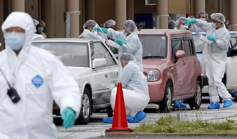 Cars which belong to evacuees, are screened for leaked radiation from the tsunami-crippled Fukushima Dai-ichi nuclear plant, after they returned to Naraha, a town outside exclusion areas,  in Fukushima prefecture, Japan,  Wednesday, June 1, 2011.  Evacuees who once lived in Kawauchi town, located within 20 kilometers from the nuclear plant,  wheeled out their cars, Wednesday, amid the nuclear crisis caused by the March 11 earthquake and tsunami.  (AP Photo/Kyodo News) JAPAN OUT, MANDATORY CREDIT, NO LICENSING IN CHINA, HONG KONG, JAPAN, SOUTH KOREA AND FRANCE