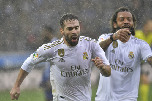 Real Madrid's Dani Carvajal, left, celebrates scoring his side's second goal with teammate Marcelo during the Spanish La Liga soccer match between Real Madrid and Alaves at Mendizorroza stadium, in Vitoria, northern Spain, Saturday, Nov. 30, 2019. (AP Photo/Alvaro Barrientos)