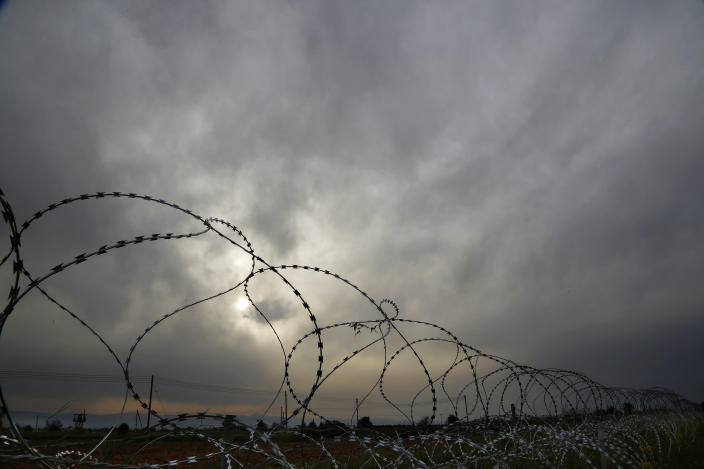 """A Cypriot military guard post is seen at left behind razor wire along the southern side of a U.N buffer zone that cuts across the ethnically divided Cyprus during sunset near village of Astromeritis, Tuesday, March 9, 2021. The government of ethnically split Cyprus has come under fire over a decision to lay razor wire along a section of a U.N. controlled buffer zone it said is needed to stem migrant inflows from the island's breakaway north, with critics charging that the """"ineffective"""" scheme only feeds partitionist perceptions amid a renewed push resume dormant peace talks. (AP Photo/Petros Karadjias)"""