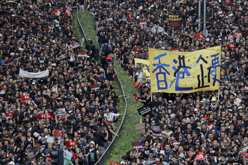 "Tens of thousands of protesters march through the streets with a banner reading ""Hong Kong stand firm"" as they continue to protest an extradition bill, Sunday, June 16, 2019, in Hong Kong. Hong Kong residents Sunday continued their massive protest over an unpopular extradition bill that has highlighted the territory's apprehension about relations with mainland China, a week after the crisis brought as many as 1 million into the streets. (AP Photo/Kin Cheung)"