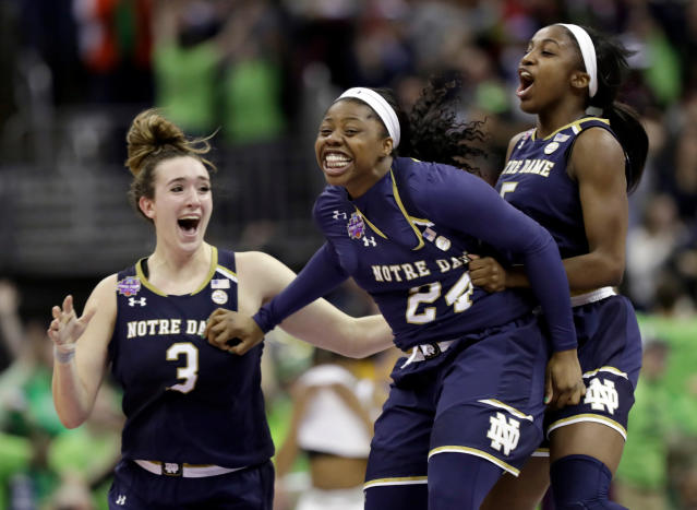 FILE - In this Sunday, April 1, 2018 file photo, Notre Dame's Arike Ogunbowale, center, is congratulated by teammates Jackie Young, right, and Marina Mabrey (3) after sinking a 3-point basket to defeat Mississippi State 61-58 in the final of the women's NCAA Final Four college basketball tournament in Columbus, Ohio. Arike Ogunbowale and Marina Mabrey will always have Columbus, Ohio. The senior guards and off-campus roommates for No. 1 Notre Dame will always have Brooklyn, too. The friendship between Ogunbowale, the Milwaukee scoring machine, and Mabrey, the street-wise Jersey shore kid, was cemented at the Barclays Center on April 17, 2015 in the Jordan Brand Classic. (AP Photo/Tony Dejak, File)