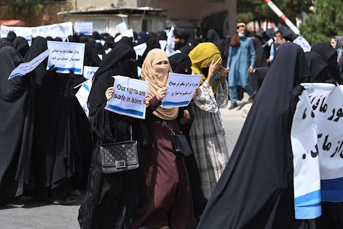 Veiled women hold banners and placards while marching during a pro-Taliban rally outside the Shaheed Rabbani Education University in Kabul on September 11, 2021.