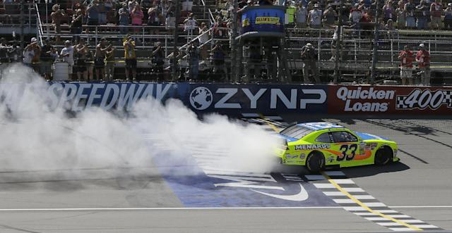 Driver Paul Menard burns rubber after winning the NASCAR Nationwide series auto race at Michigan International Speedway in Brooklyn, Mich., Saturday, June 14, 2014. (AP Photo/Carlos Osorio)