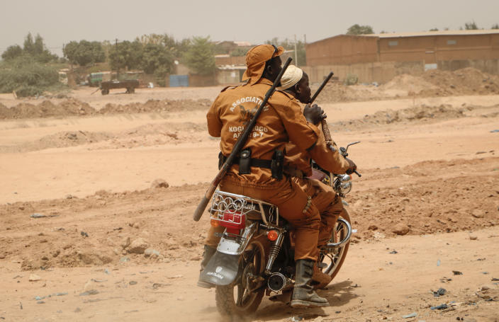 Local defense force fighters drive on a motorbike during an event to inaugurate a new chapter of the group in Ouagadougou, Burkina Faso, Saturday, March 14, 2020. In an effort to combat rising jihadist violence, Burkina Faso's military has recruited volunteers to help it fight militants. (AP Photo/Sam Mednick)