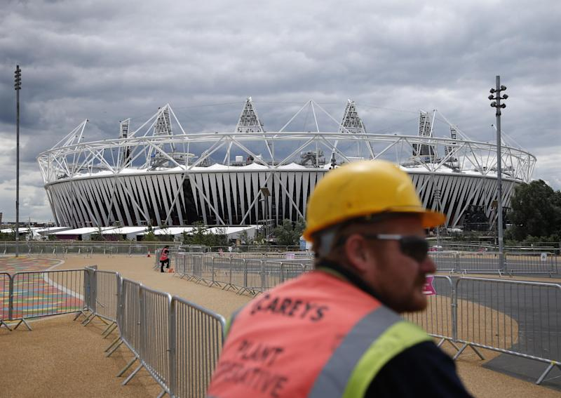 A construction worker stands outside the Olympic Stadium as preparations continue for the 2012 Summer Olympics, Sunday, July 15, 2012, in London. (AP Photo/Jae Hong)
