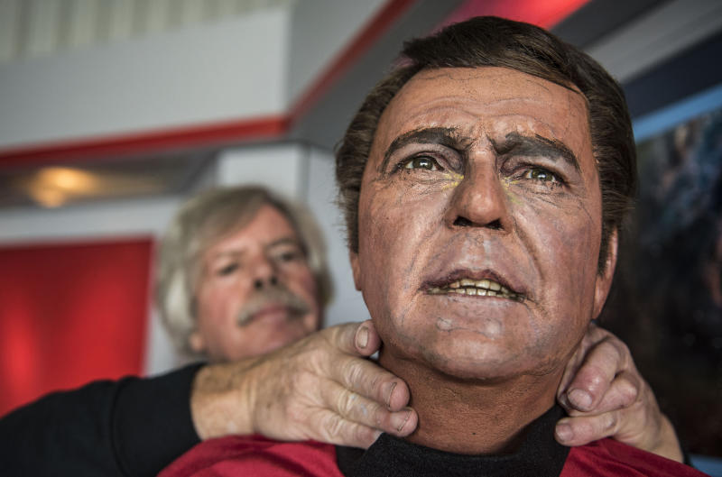 In this Saturday, March 25, 2017 photo, Steve Greenthal adjusts the wax head of Star Trek character Scotty at the Fullerton Airport in Fullerton, Calif. The Orange County Register says the figures were crafted for the Movieland Wax Museum in Buena Park, which auctioned everything off when it closed about a decade ago. (Nick Agro/The Orange County Register via AP)