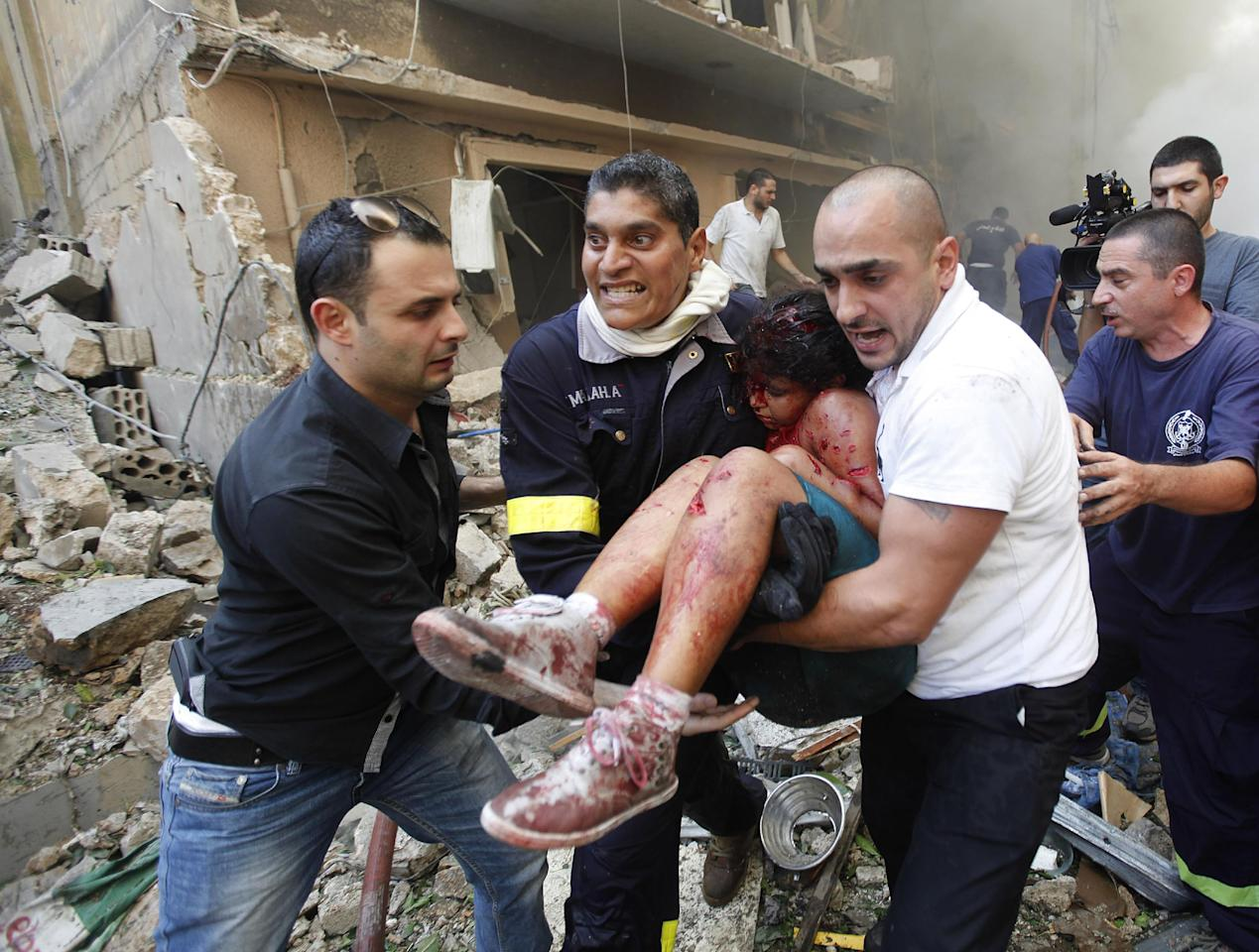 Lebanese rescue workers and civilians carry an injured girl from the scene of an explosion in the mostly Christian neighborhood of Achrafiyeh, Beirut, Lebanon, Friday Oct. 19, 2012. Lebanon's state news agency says a car bomb in east Beirut has killed at least six people and wounded scores in the worst blast the city has seen in years, coming at a time when Lebanon has seen a rise in tension and eruptions of clashes stemming from the civil war in neighboring Syria.(AP Photo/Hussein Malla)