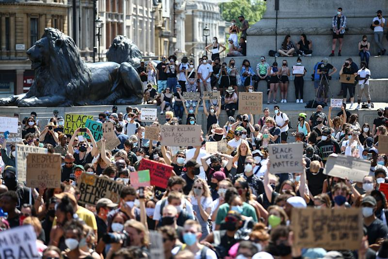 People in London hold placards as they join a spontaneous Black Lives Matter march at Trafalgar Square on May 31, 2020.