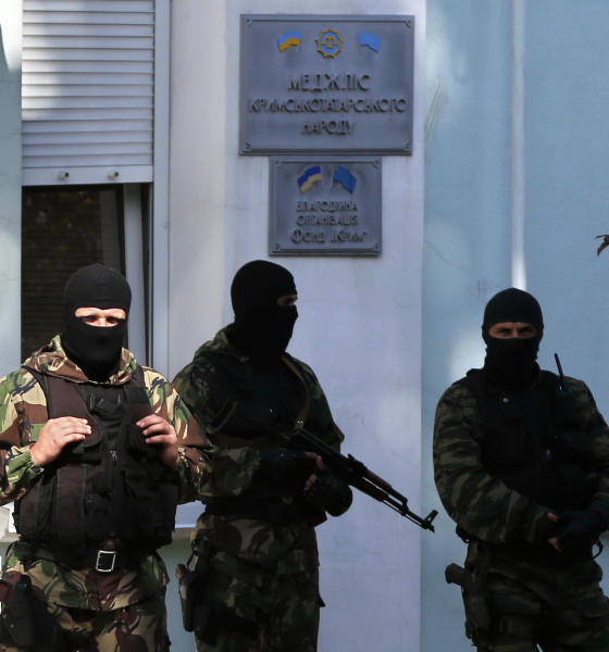 Armed men stand guard in front of the entrance of the Mejlis of the Crimean Tatar people in Simferopol on September 16, 2014 (AFP Photo/Max Vetrov)