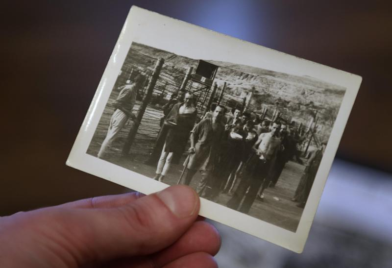 In this Tuesday, April 2, 2013 photo filmmaker Matthew Nash, hand only, holds a 1945 photograph, in his Boston home, that shows survivors at what is believed to be the Nazi Mauthausen concentration camp. The photo was taken by Nash's grandfather U.S. Army medic Donald Johnson. Nash's discovery of photographs by his grandfather led him to create a documentary about the liberation of the Ohrdruf concentration camp in Germany, the first that the Americans found. (AP Photo/Steven Senne)