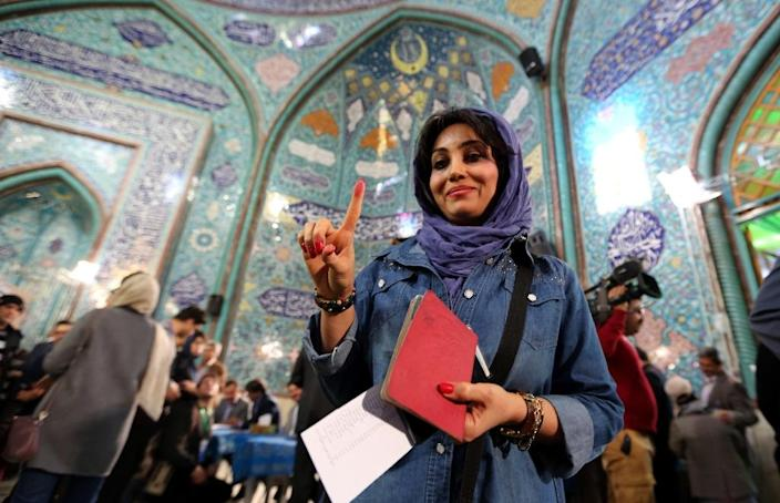 An Iranian woman shows her inked finger after casting her ballot at a polling station in Tehran on February 26, 2016 (AFP Photo/Atta Kenare)