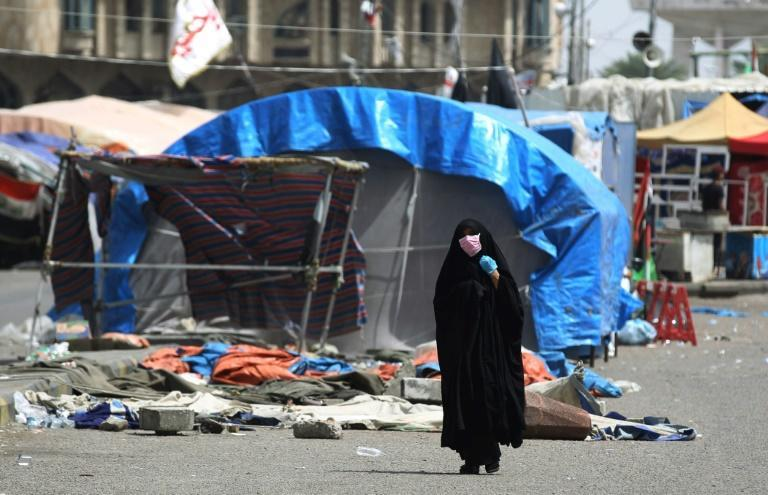 A woman in Baghdad wearing a mask walks in an empty street in April 2020 where months before anti-government protests were taking place (AFP Photo/AHMAD AL-RUBAYE)