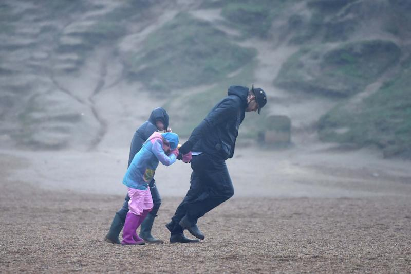 A man and children walk against the wind as Storm Ciara arrives (Getty Images)