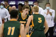 North Dakota State forward Rocky Kreuser (34) center, celebrates his 3-point basket with Jarius Cook (11) and Sam Griesel (5) as head coach David Richman, right rear, and the rest of the bench look on in the second half of an NCAA college basketball game against TCU in Fort Worth, Texas, Tuesday, Dec. 22, 2020. (AP Photo/Tony Gutierrez)