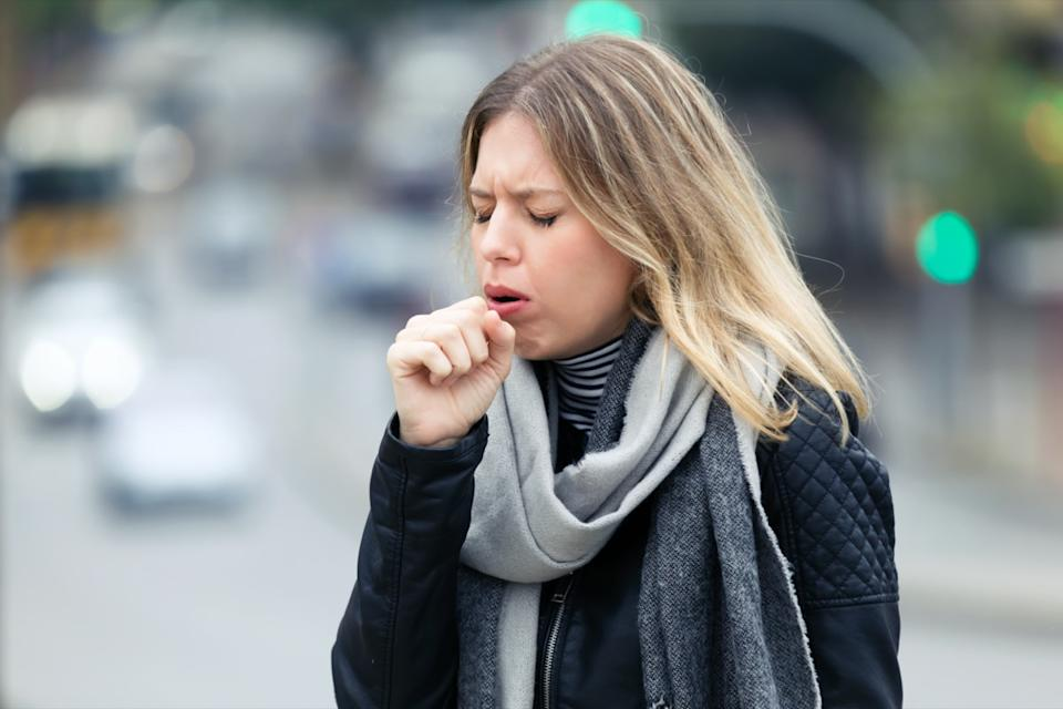 Shot of illness young woman coughing in the street.
