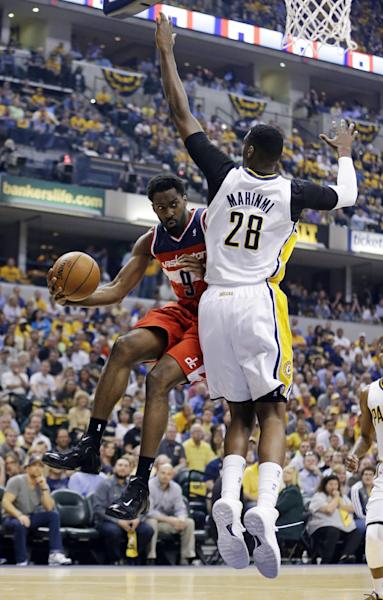 Washington Wizards forward Martell Webster, left, makes a pass around Indiana Pacers center Ian Mahinmi during the first half of game 2 of the Eastern Conference semifinal NBA basketball playoff series Wednesday, May 7, 2014, in Indianapolis. (AP Photo/Darron Cummings)