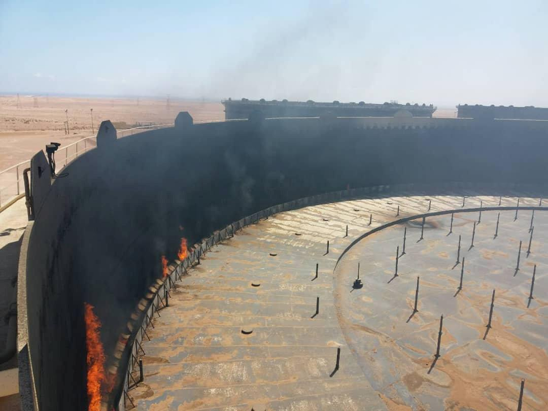 Smoke and flame rise from an oil storage tank that was set on fire amid fighting between rival factions at Ras Lanuf terminal, Libya in this handout picture released on June 16, 2018. The National Oil Corporation/ Handout via Reuters ATTENTION EDITORS - THIS PICTURE WAS PROVIDED BY A THIRD PARTY. REUTERS IS UNABLE TO INDEPENDENTLY VERIFY THIS IMAGE.