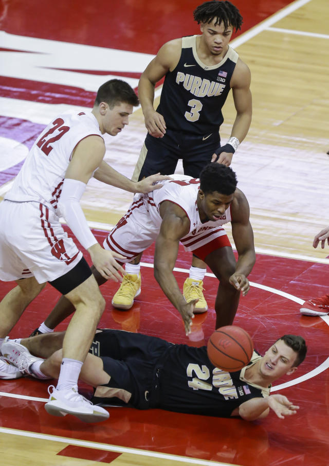 Purdue's Grady Eifert (24) passes the ball away from Wisconsin's Ethan Happ (22) and Khalil Iverson during the first half of an NCAA college basketball game Friday, Jan. 11, 2019, in Madison, Wis. (AP Photo/Andy Manis)