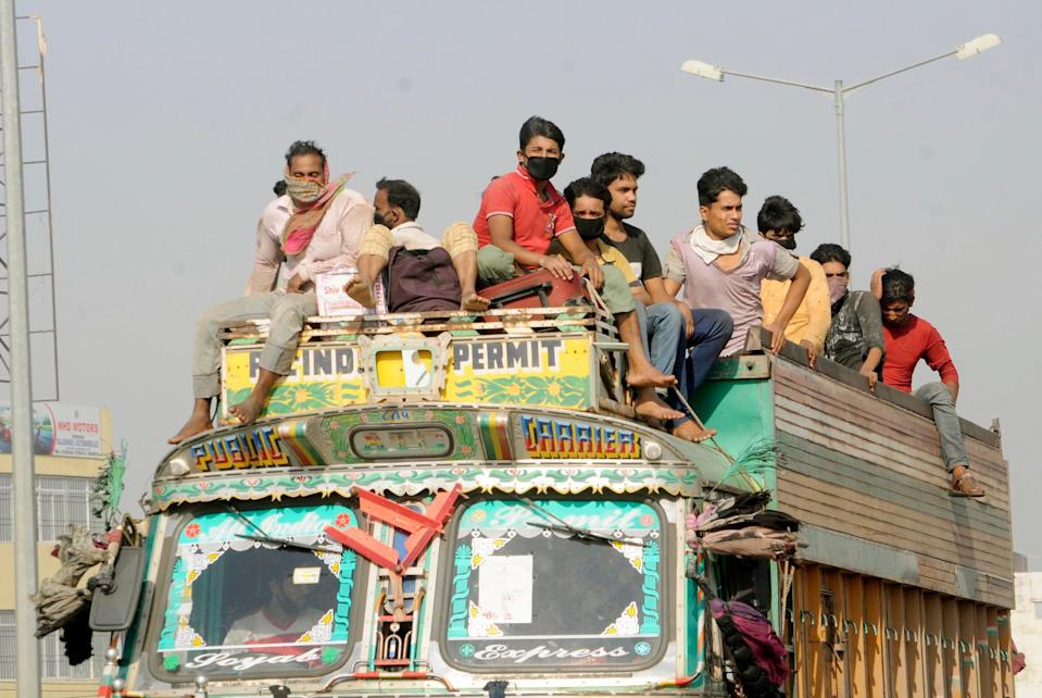 Migrants workers occupy every spare spot aboard trucks in Patna, India, as they attempt to get home during the coronavirus lockdown on May 17, 2020.