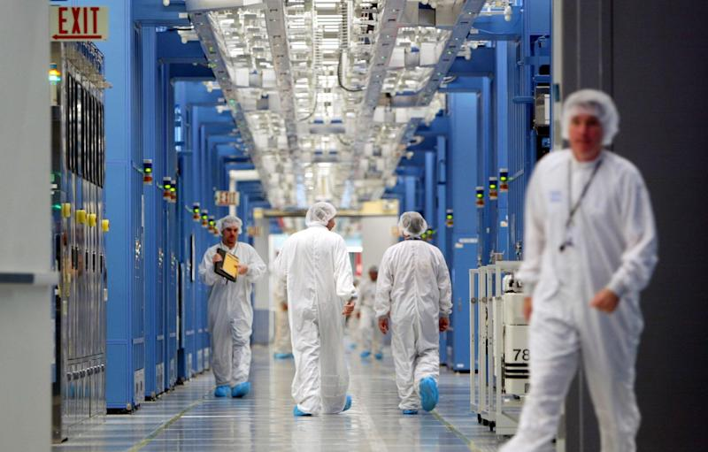 IBM workers walk in an IBM 12-inch wafer chip fabricating plant July 20, 2004 in Fishkill, New York: Mario Tama/Getty Images