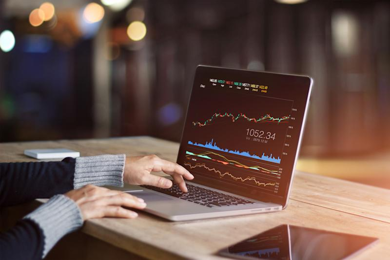 Close-up of two hands tracking a stock chart on a laptop computer.