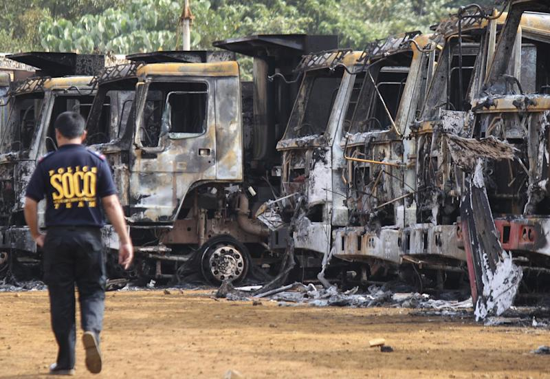 A Filipino investigator walks beside trucks that were allegedly burned by communist rebels at the compound of the Platinum Group Metals Corporation in Surigao del Norte province, southern Philippines on Tuesday Oct. 4, 2011. Philippine President Benigno Aquino III has ordered security for mining companies beefed up after a big raid by communist rebels shut down operations of Nickel Asia Corp., the country's largest nickel producer and sent its stock plummeting. (AP Photo/Roel Catoto)