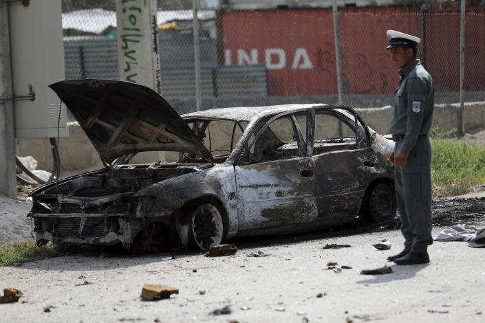 Afghan traffic police stand near a damaged vehicle where rockets were fired from in Kabul, Afghanistan, Tuesday, July 20, 2021. At least three rockets hit near the presidential palace on Tuesday shortly before Afghan President Ashraf Ghani was to give an address to mark the Muslim holiday of Eid-al-Adha. (AP Photo/Rahmat Gul)