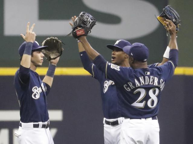 Milwaukee Brewers' Keon Broxton, Christian Yelich and Curtis Granderson celebrate after a baseball game against the Cincinnati Reds Wednesday, Sept. 19, 2018, in Milwaukee. The Brewers won 7-0. (AP Photo/Morry Gash)