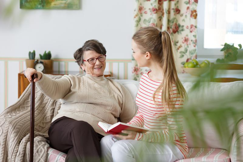 Older woman with a cane sitting on couch next to a younger woman reading a book