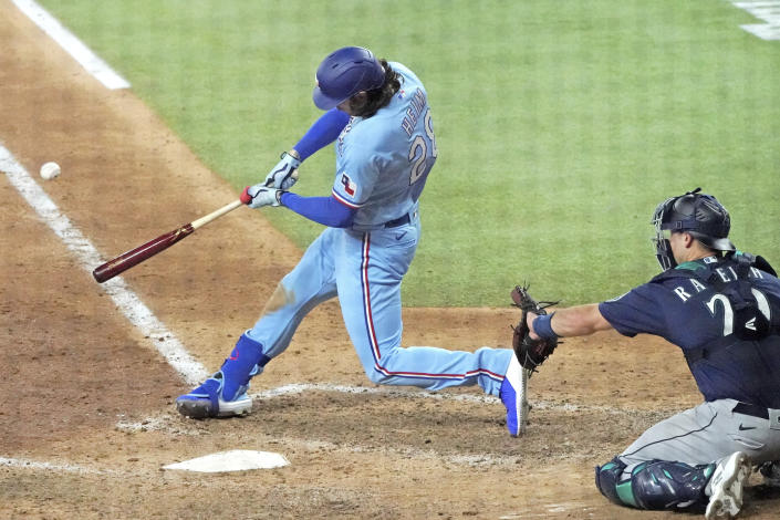 Texas Rangers designated hitter Jonah Heim hits a winning home run against the Seattle Mariners in the ninth inning of a baseball game Sunday, Aug. 1, 2021, in Arlington, Texas. (AP Photo/Louis DeLuca)