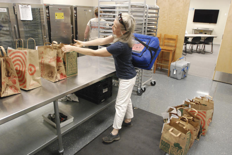 In this photo taken Friday, June 14, 2019, volunteers including 60-year-old Laura Orchard pick up food packages to deliver to homebound families and dependent children in Santa Fe, N.M., at the headquarters for Kitchen Angels. An annual report on childhood well-being from the Annie E. Casey Foundation ranks New Mexico last among 50 states that includes measures of poverty, health care, education and family support. The number of children living in poverty has swelled over the past three decades in fast-growing, ethnically diverse states such as Texas, Arizona and Nevada as the nation's population center shifts south and west. (AP Photo/Morgan Lee)