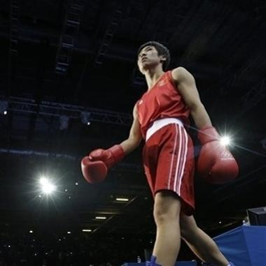 China's Ren Cancan walks to the ring to fight  Russia's Elena Savelyeva during a women's flyweight 51-kg quarterfinal boxing match at the 2012 Summer Olympics, Monday, Aug. 6, 2012, in London. (AP Photo/Patrick Semansky)
