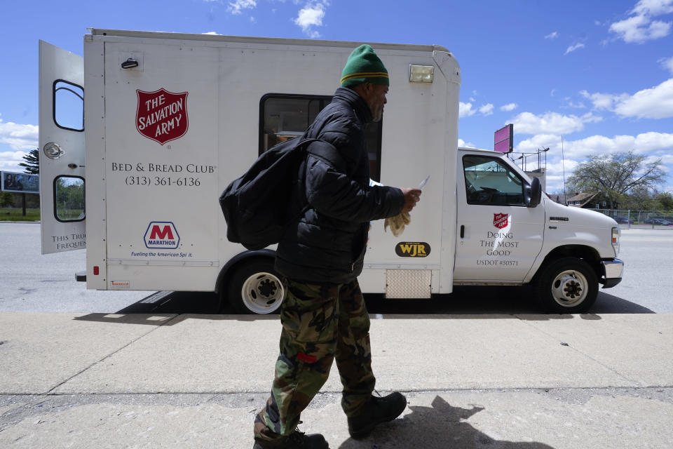A pedestrian collects a bagged meal at a Salvation Army Bed & Bread truck in Detroit, Wednesday, May 12, 2021. In three weeks, more than 40 people have received vaccinations through the program to reach people who normally have little to no access to churches, community centers or other places where vaccines are being given. Mobile care teams consisting of two nurses and a peer support specialist accompany The Salvation Army's Bed & Bread trucks as they cruise Detroit, which lags far behind the state and nearby communities in percentage of people vaccinated. (AP Photo/Paul Sancya)
