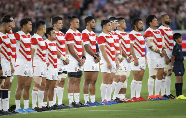 Japanese players take a minutes silence for the victims of Typhoon Hagibis prior to the start of the Rugby World Cup Pool A game at International Stadium between Japan and Scotland in Yokohama, Japan, Sunday, Oct. 13, 2019. (AP Photo/Christophe Ena)
