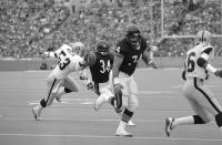 FILE - In this Nov. 4, 1984, file photo, Chicago Bears running back Walter Payton, (34), eludes Los Angeles Raiders linebacker Rod Martin (53) as he follows blocking of Bears tackle Jim Covert (74) to score his second touchdown in the first half of an NFL football game at Soldier Field in Chicago. Covert made the people he played alongside look good, and after a nearly two-decades-long wait, the tough Chicago Bears left tackle will join them in the Pro Football Hall of Fame. (AP Photo/Steve Green, File)