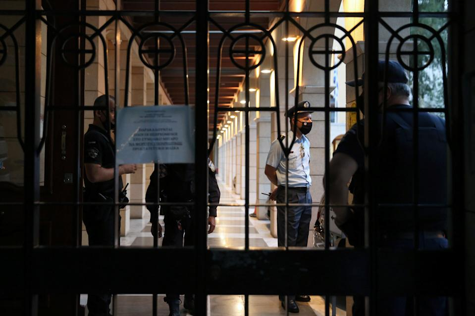 Police officers are seen at the entrance of Petraki Monastery (REUTERS)