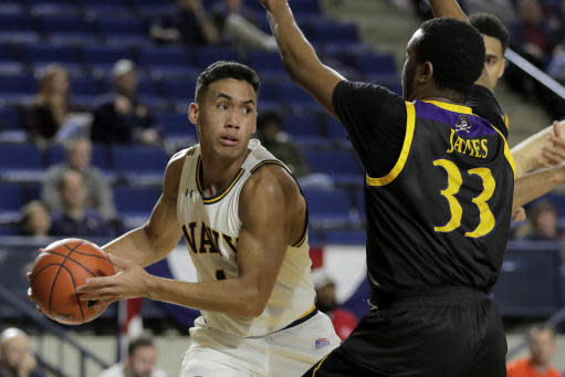 Navy guard John Carter Jr., left, drives in the paint against East Carolina guard Miles James (33) during the first half of an NCAA college basketball game at the Veterans Classic Tournament, Friday, Nov. 8, 2019, in Annapolis, Md. (AP Photo/Julio Cortez)